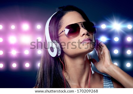 Portrait of woman dj enjoying music on headphones and nightclub lights - stock photo