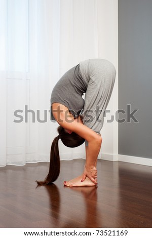 portrait of woman doing flexibility exercise in room - stock photo