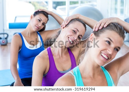 Portrait of woman doing head exercise with her friends in fitness studio - stock photo