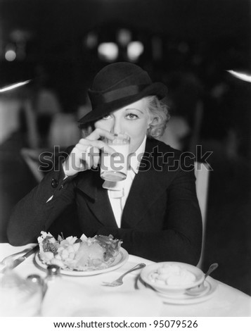 Portrait of woman drinking and eating in restaurant - stock photo