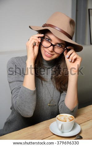 portrait of woman drinking cappuccino coffee cup in hands on light brown wooden table cafe