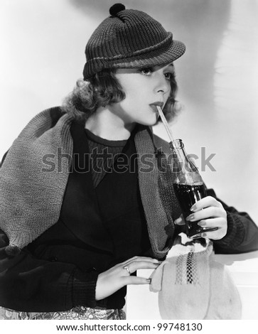 Portrait of woman drinking from bottle of soda - stock photo