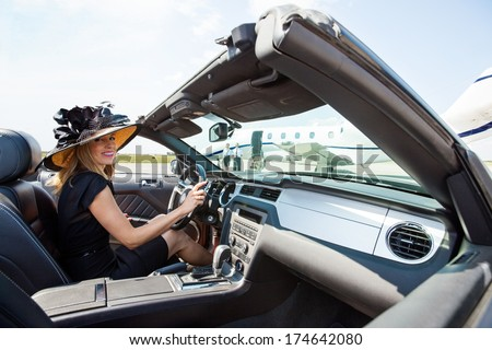 Portrait of woman driving convertible towards private jet at airport terminal - stock photo