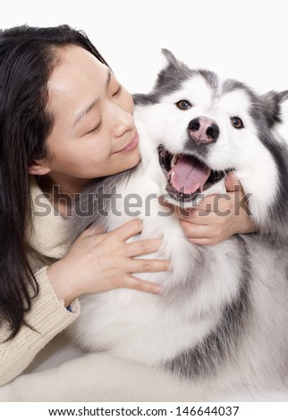 Portrait of woman embracing her dog, studio shot
