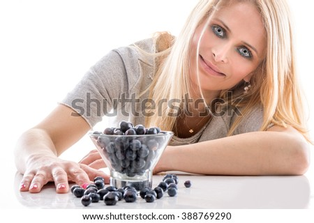 Portrait of Woman enjoying eating her  blueberries isolated on white background