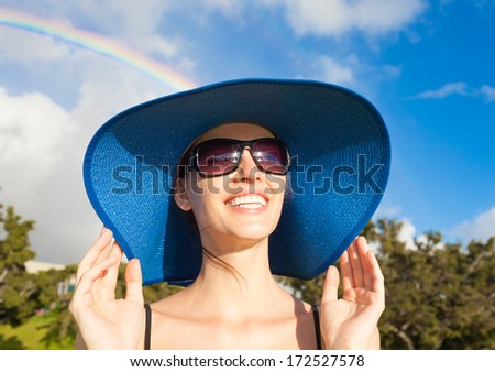 Portrait of woman enjoying the sun after the storm with a beautiful rainbow in the background.