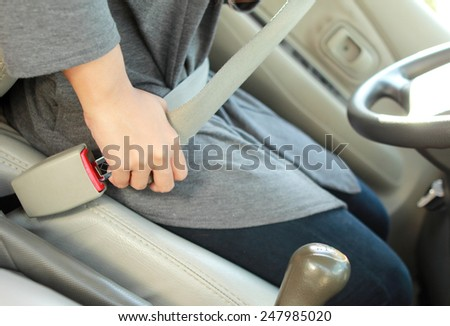 portrait of woman hand putting on safety belt - stock photo