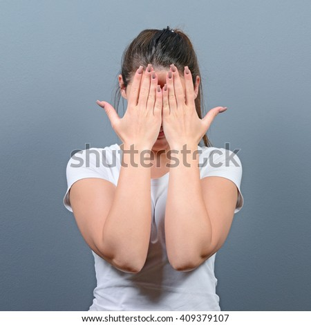Portrait of woman hiding her face with both hands against gray background
