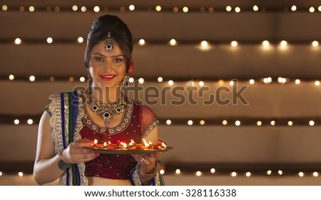 Portrait of woman holding a tray of diyas - stock photo