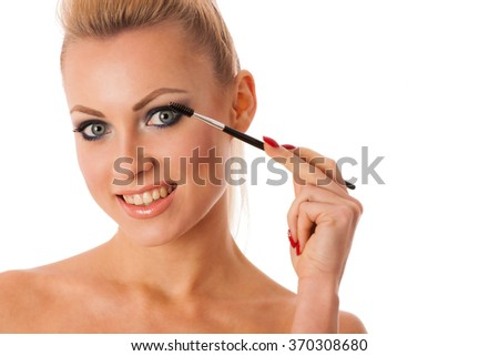 Portrait of woman holding beauty accessories, mascara, powder brush, lipstick, for perfect makeup, smokey eyes, full lips.