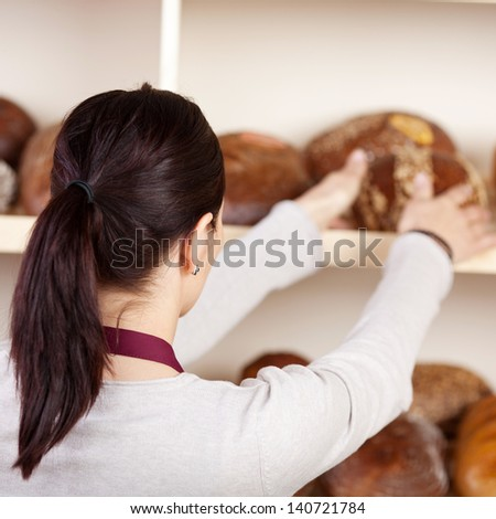 Portrait of woman holding bread in a rear view shot