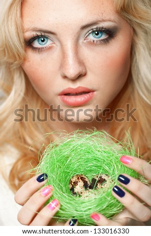 portrait of woman holding  green nest with quail eggs - stock photo