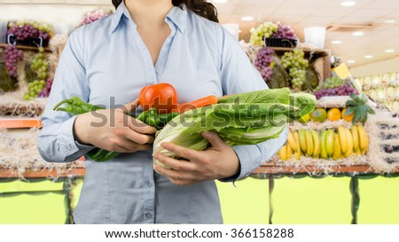 portrait of woman holding in her arms vegetables like lettuce tomatoes and peppers at the greengrocer on the background - stock photo
