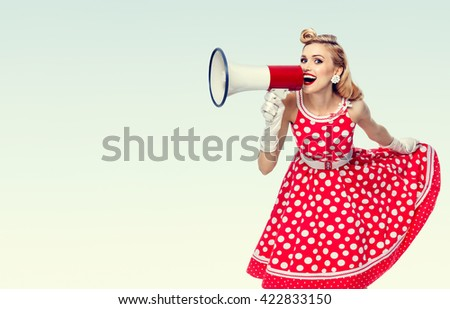 Portrait of woman holding megaphone, dressed in pin-up style red dress in polka dot and white gloves, with blank copyspace area for text or slogan. Model posing in retro fashion vintage studio shoot.