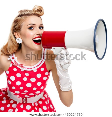 Portrait of woman holding megaphone, dressed in pin-up style red dress in polka dot and white gloves, isolated on white background. Caucasian blond model posing in retro fashion vintage studio shoot.