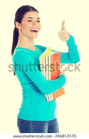 Portrait of woman holding notes showing thumbs up. - stock photo