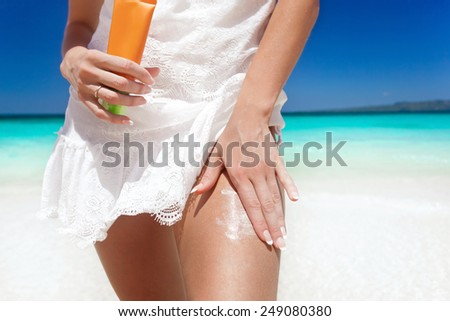 Portrait of woman holding sunscreen cream on beach, beauty concept - stock photo