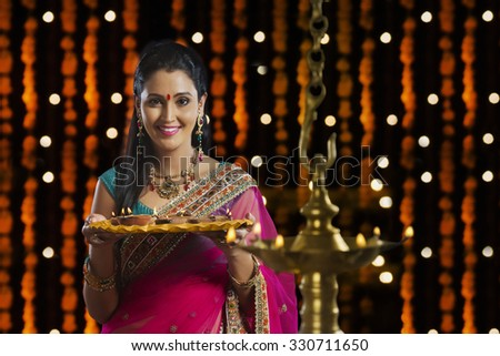 Portrait of woman holding tray of diyas - stock photo
