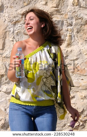 Portrait of woman holding water bottle and laughing - stock photo