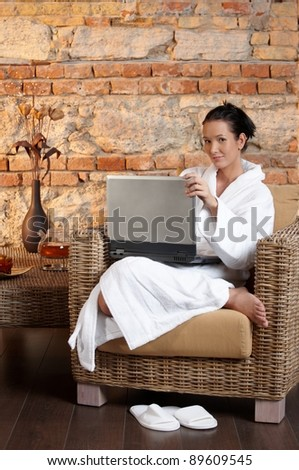 Portrait of woman in bathrobe sitting in armchair with laptop computer, smiling.?