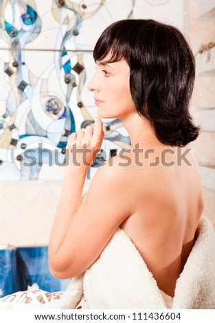 Portrait of woman in bathroom wrapped in mantle - stock photo
