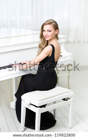 Portrait of woman in black dress sitting and playing piano. Concept of music and art - stock photo