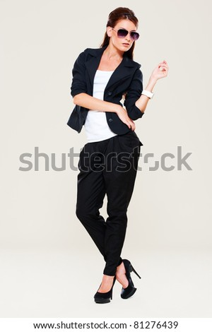 portrait of woman in black suit and sunglasses - stock photo
