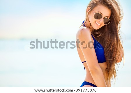 Portrait of woman in black swim posing on tropical beach - stock photo