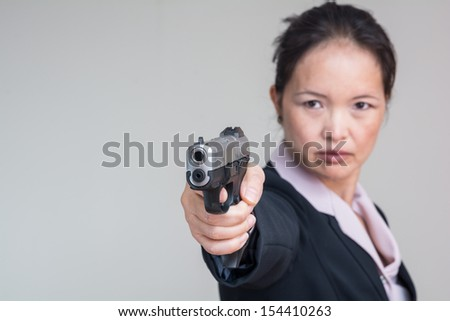 Portrait of woman in business suit aiming a gun with one hand