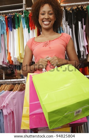 Portrait of woman in clothing store with bags - stock photo