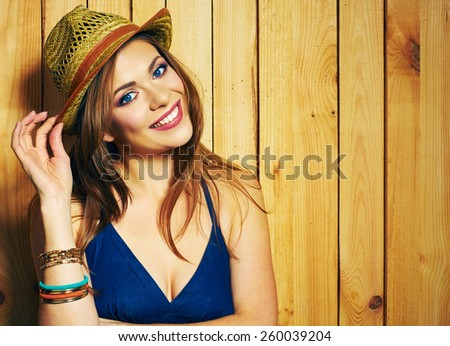 Portrait of woman in  Country style. Smiling young female  model posing against wooden background. - stock photo