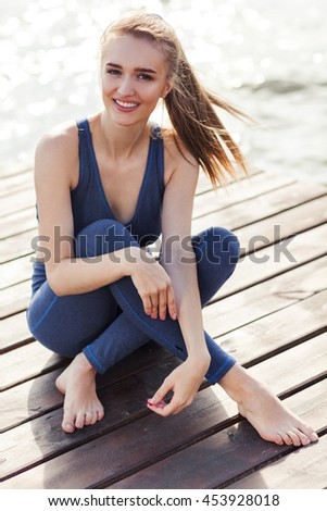 Portrait of woman in fitness wear near the sea - stock photo