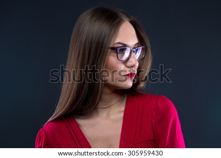 Portrait of woman in glasses, looking away on black background