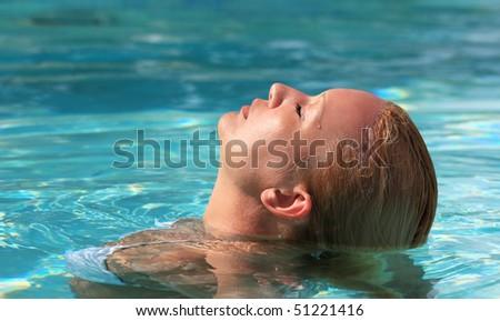 Portrait of woman in white bikini relaxing in swimming pool - stock photo