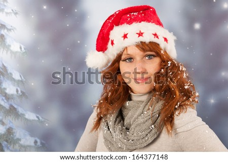 Portrait of woman in winter with snow and hat of Santa Claus