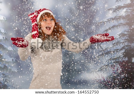 Portrait of woman in winter with snow and Santa Claus hat at snowstorm