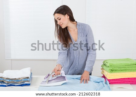 Portrait  of woman ironing clothes in house - stock photo