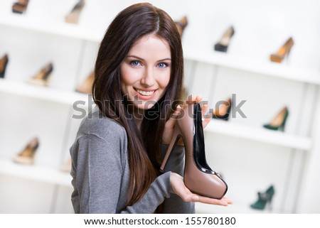 Portrait of woman keeping coffee-colored leather pump in shopping center - stock photo