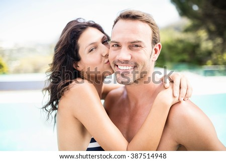 Portrait of woman kissing man near pool on a sunny day