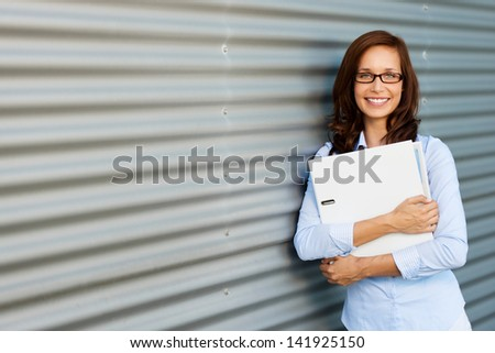 Portrait of woman leaning on the wall and holding a laptop - stock photo
