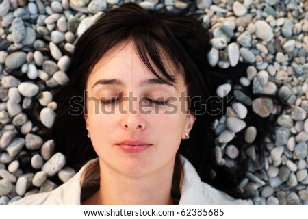 Portrait of woman lie on the stone beach with eyes closed - stock photo