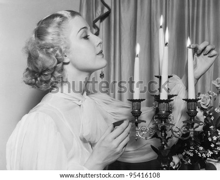 Portrait of woman lighting candles - stock photo