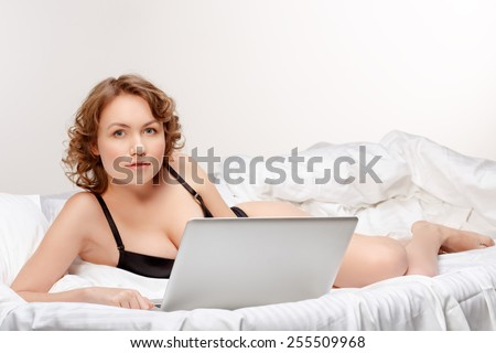 Portrait of woman lying on bed with a laptop. - stock photo