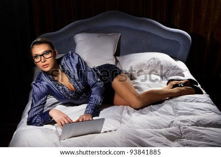 Portrait of woman lying on bed with a laptop - stock photo