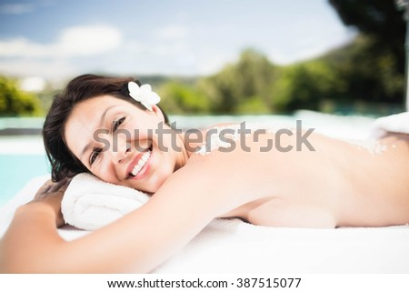 Portrait of woman lying on massage table with salt scrub on back in a spa