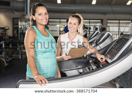 Portrait of woman on treadmill and trainer at the gym - stock photo