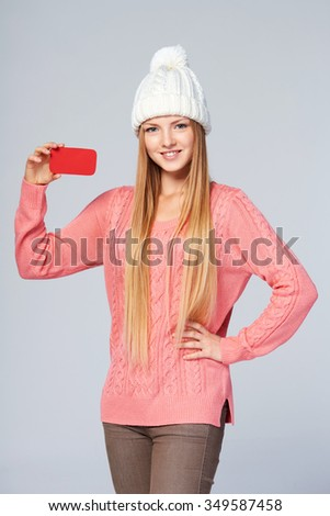 Portrait of woman on white background wearing woolen hat and sweater showing blank credit card - stock photo