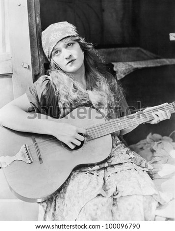 Portrait of woman playing guitar - stock photo
