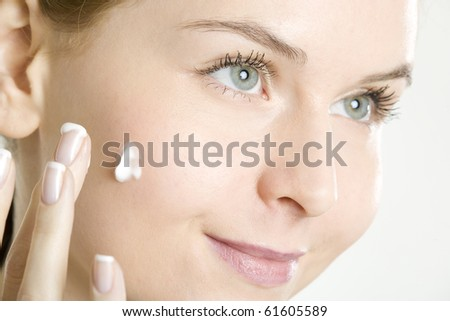 portrait of woman putting cream on face - stock photo