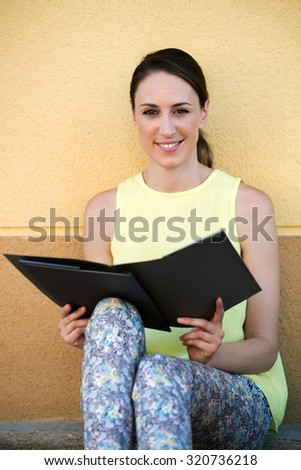 portrait of woman reading pamphlet or magazine in the street / Attractive young woman sitting in the street reading a brochure - stock photo